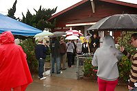 Tuesday, November 4 2008.  Poll workers stand  in the rain outside Ocean Beach Womens Club on Bacon Street to help OB Voters find their polling station on Election Day, November 4 2008.  Some determined OB residents endured long lines and pouring rain as they waited to vote at the station.  Rain fell early in San Diego on what is expected to be a record-breaking day at the polls.