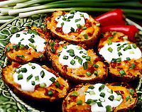 Twice Baked potatos garnished with cheese, bacon, sour cream and chopped green onions, on a green plate, studio.