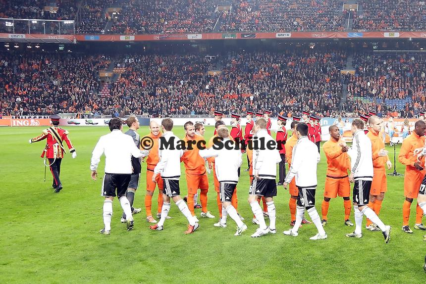 Mannschaften begruessen sich auf dem Feld der Amsterdam ArenA