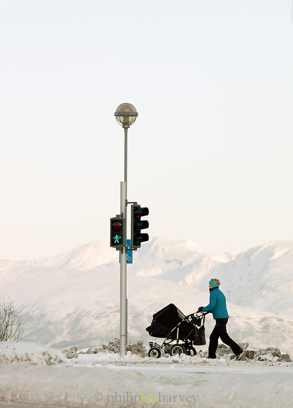 A woman pushes a pram down the frozen streets of Tromso, Norway