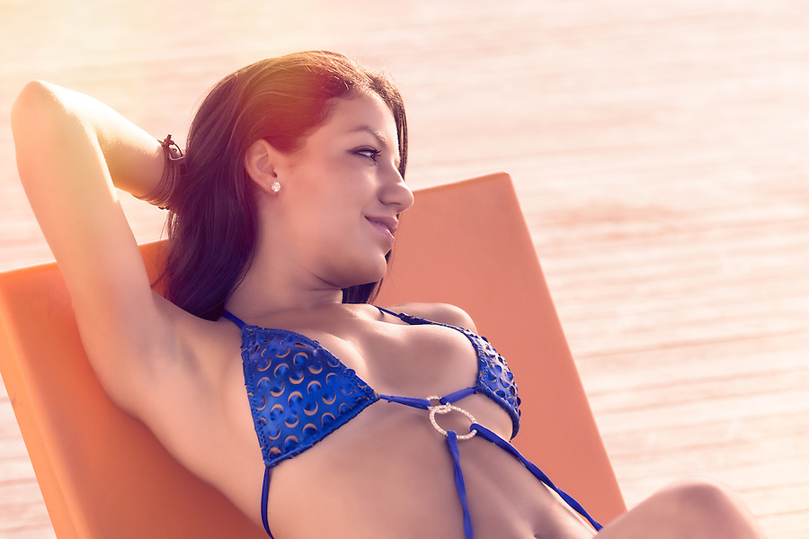 Young and sensual hispanic woman tanning in the beach