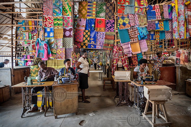 Tailors at work in a city market which sells fabrics and clothes made in traditional designs.