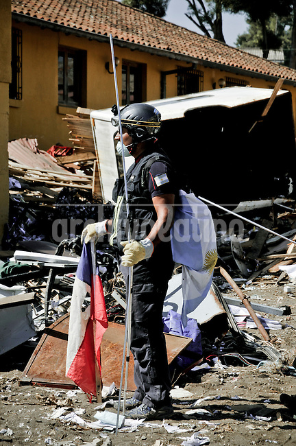 Chile, Aftermath of the tsunami in the area of Consitucion.Argentina fireman looking for dead body.