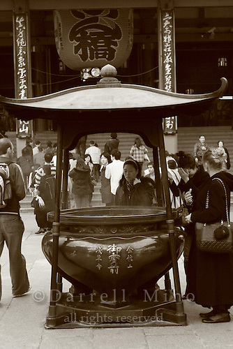 Mar 6, 2006; Tokyo, JPN; Asakusa.Visitors gather around a large bronze incense bowl in front of the Senso-ji temple and waft the smoke (considered to be the breath of the gods) upon themselves for its supposed curative powers...Photo credit:  Darrell Miho
