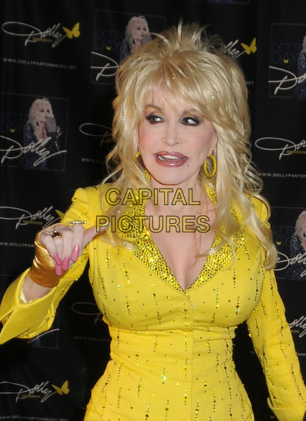 Dolly Parton signs autographs for a limited number of lucky fan winners during the 2011 CMA Music Festival at Fan Fair Exhibit Hall at the Nashvile Convention Center, marking her first autograph session at the event since the mid-'70s. Nashville, Tennessee, USA 11th June 2011.half length yellow dress gold pink nail varnish polish jacket beads beaded.CAP/ADM/LF.©Laura Farr/AdMedia/Capital Pictures.