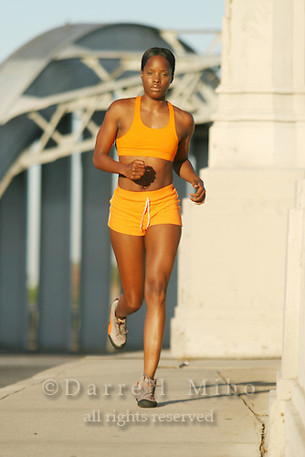 Model: LaKreshia Hart<br /> Orange running outfit.  Running on the Sixth Street bridge.<br /> <br /> Photo Credit Darrell Miho.<br /> &copy; Darrell Miho