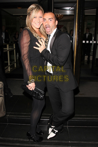 GUEST & LOUIE SPENCE .At the Sony Radio Academy Awards, Grosvenor House Hotel, Park Lane, London, England, UK, May 10th 2010..full length black suit tie white shirt hand claw funny pose  shoes .CAP/AH.©Adam Houghton/Capital Pictures.