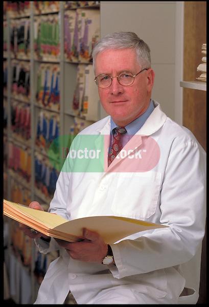portrait of elder doctor reading charts