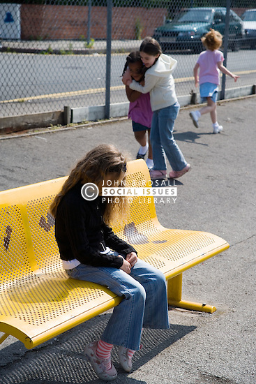 Girl sitting alone on bench in school playground looking sad,