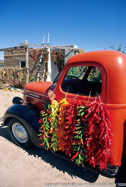A red pickup truck serves as a dramatic compliment to  colorful strings of chiles, called ristras, drying in the sun at a fruit stand in the northern New Mexico village of Velarde.