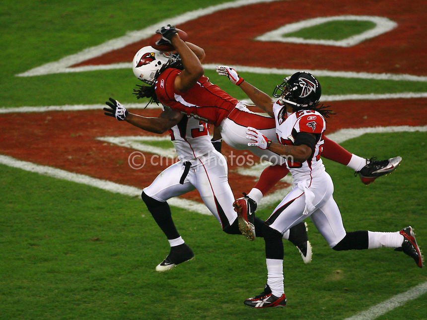 Jan 03, 2009; Glendale, AZ, USA; Arizona Cardinals wide receiver Larry Fitzgerald (11) catches a touchdown pass over Atlanta Falcons cornerback Chris Houston (23) and another Falcons defensive back in the first quarter of the NFC Wild Card Playoff Game at University of Phoenix Stadium.