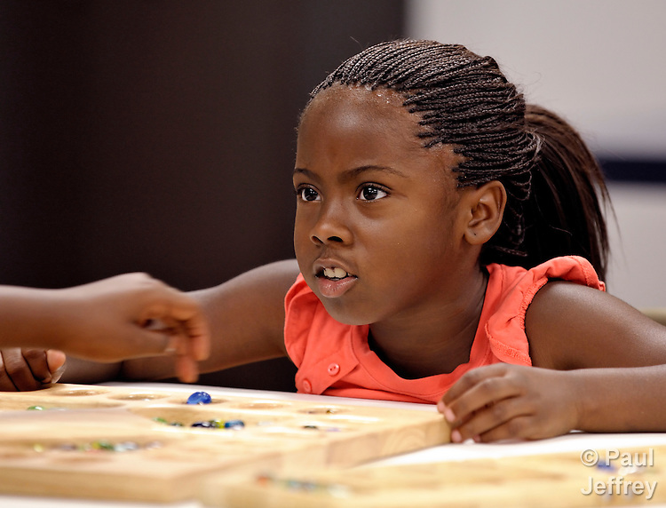 A girl plays a table game in the Mary E. Brown Center, part of the Lessie Bates Neighborhood House in East St. Louis, Illinois.