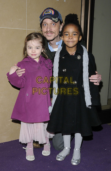 "Mackenzie Crook & his daughters.The ""Sofia The First"" Disney channel TV launch screening, May Fair Hotel, Stratton St., London, England..February 22nd, 2013.full length black pink dress coat grey gray scarf baseball cap hat father dad kids children crouching jacket coat.CAP/CAN.©Can Nguyen/Capital Pictures."