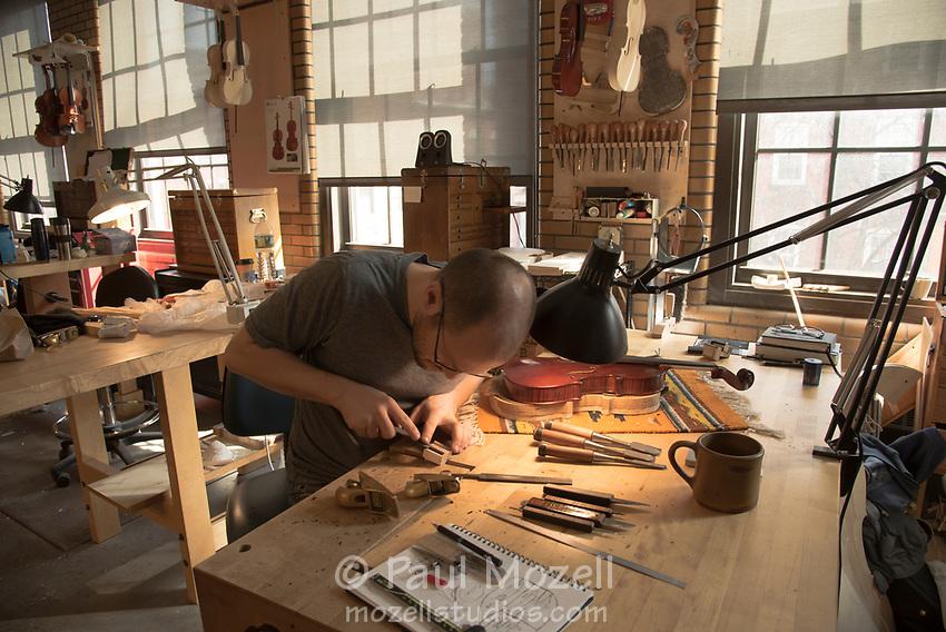 Ryan Hamonds uses a small hand plane to create violin parts at the North Bennett Street School, Boston.