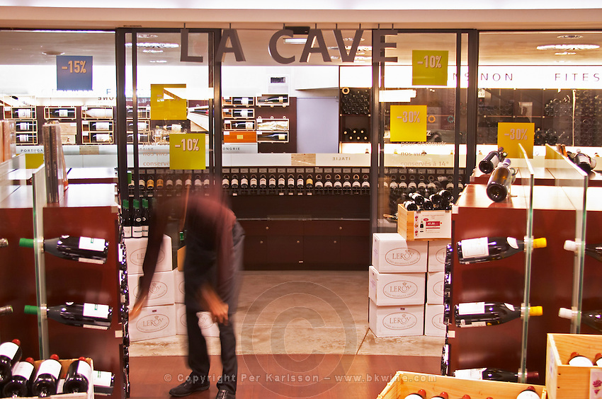 The entrance to the special temperature controlled wine cellar La Cave, called La Cave a 14 since it keeps fourteen degrees centigrade. In the foreground bottles, boxes and shelves and a sommelier, shop attendant staff blurred and moving. Signs with special promotions 10 ten % percent discount. The Lavinia wine shop in Paris. Probably the biggest wine shop in Paris, with its special temperature controlled section for wines that are fragile and must be stored at cool low temperature.