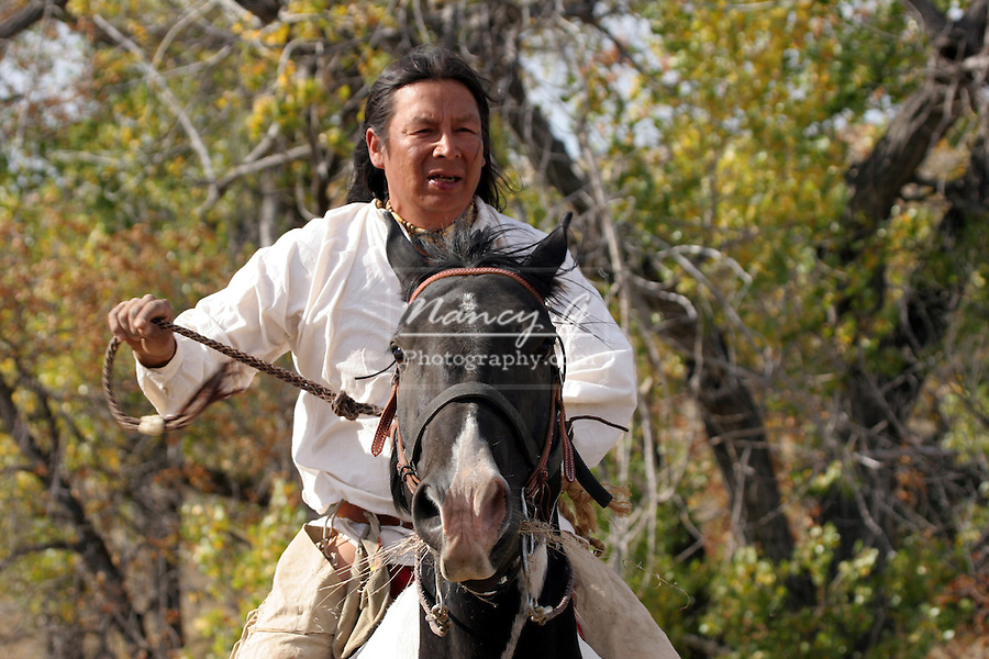 A Native American Indian man riding his Indian pony bareback