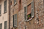 Windows with pale blue shudders on an old brick building in Como, Italy