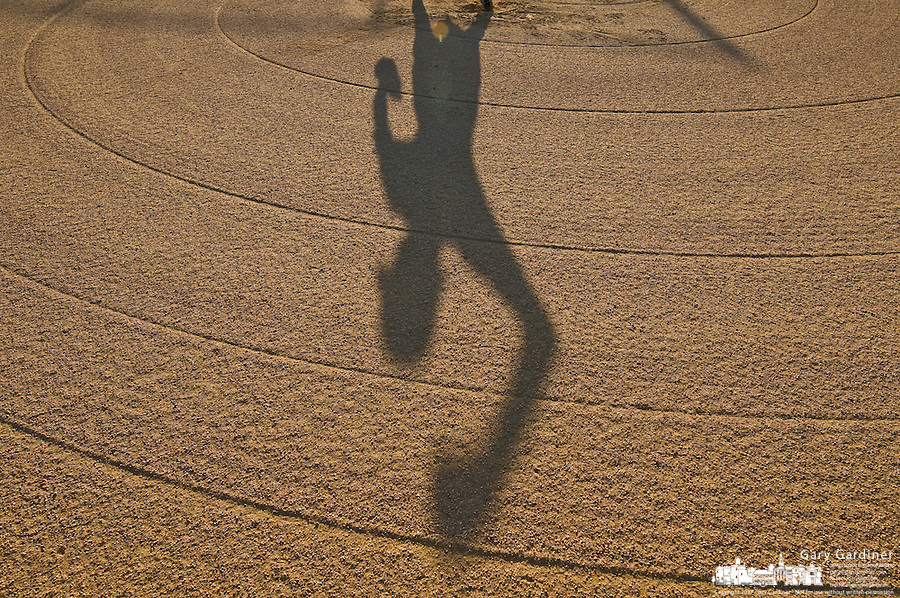 The pitcher's shadow during team practice is cast across a recently graded infield at a community baseball field