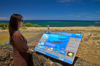 woman visitor looking at Hawaiian Islands Humpback Whale National Marine Sanctuary sign, Puukohola Heiau National Historic Site, Kawaihae, Kohala, Big Island, Hawaii, USA, Model Released - MR#: 000103