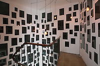 This stairwell has been used to exhibit an installation of black lacquer squares of differing sizes illuminated by a series of bare light bulbs