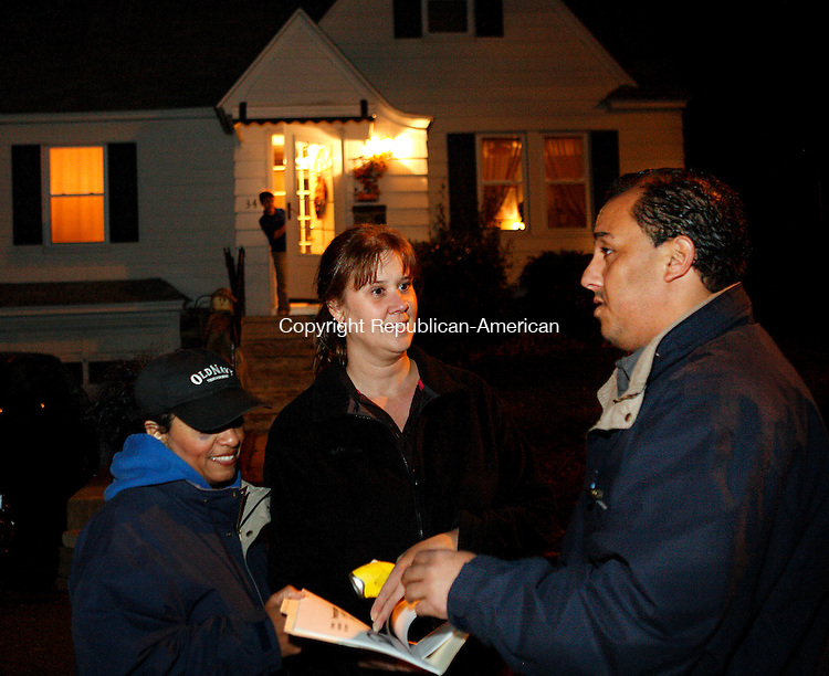 WATERBURY, CT 30 October 2008-103108CM03--Angel Ortiz, right, reviews neighborhood watch information with fellow residents, Carmella Quinones, left and Eileen Kling.  Oritz formed the neighborhood watch following recent car break-ins, speeding and other crimes that have plagued this east side Waterbury neighborhood in the recent weeks.    <br /> Christopher Massa Republican-American