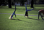 Teenage girls doing handstands in the park