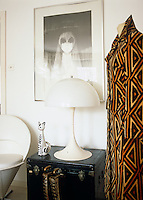 A black and white 70's print hangs above a lamp beside a coat designed by Roberta di Camerino displayed on a mannequin