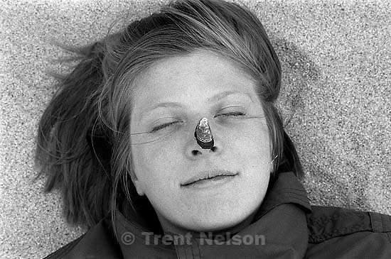 Laura Nelson with a shell on her nose on the beach.<br />