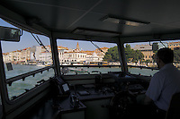 The cockpit and pilot of a Vaporetti / water bus, looking through window towards Vaporetti station..Venice Italy.