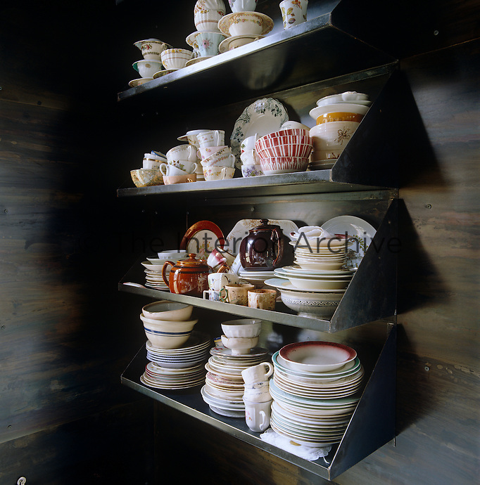 Detail of steel shelves stacked with crockery on the hand patinated steel walls of the dining area