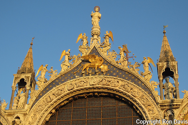 Saint Marc and angels statues crowning the central arch of Basilica San Marco, with the Lion of St Marc.