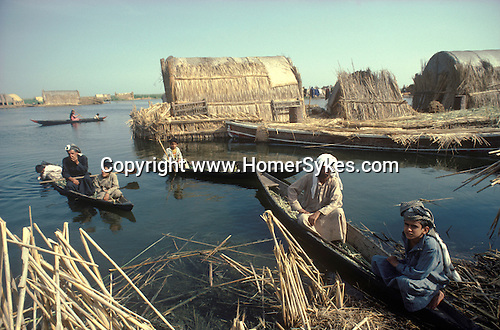 Marsh Arabs. Southern Iraq. Circa 1985. Marsh Arab men. Children and fathers in boats. Reed building on small artificial island called a kibasha. Permanent island called a dibin. Haur al Mamar or Haur al-Hamar marsh collectively known now as Hammar marshes Irag 1984