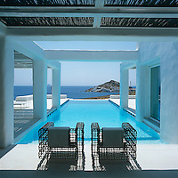 Long shadows are cast by two metal mesh chairs looking out over an infinity pool with views of the Mediterranean