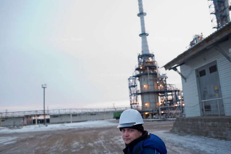 A Bashneft employee walks near equipment at a Bashneft oil refinery in Ufa, Bashkortostan, Russia. The area is a major oil and gas producing region in the country.