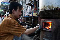 Young man adding charcoal to an outdoor stove in the Muslim district of Daqingzhen Si in Xi'an, Shaanxi, China.
