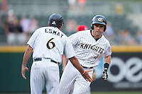 Vinny Rottino (4) of the Charlotte Knights is congratulated by third base coach Tim Esmay (6) after hitting a home run against the Syracuse Chiefs at BB&T BallPark on June 1, 2016 in Charlotte, North Carolina.  The Knights defeated the Chiefs 5-3.  (Brian Westerholt/Four Seam Images)