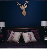 A wooden stag's head by Dan Marty Designs hangs above the bed in the guest bedroom