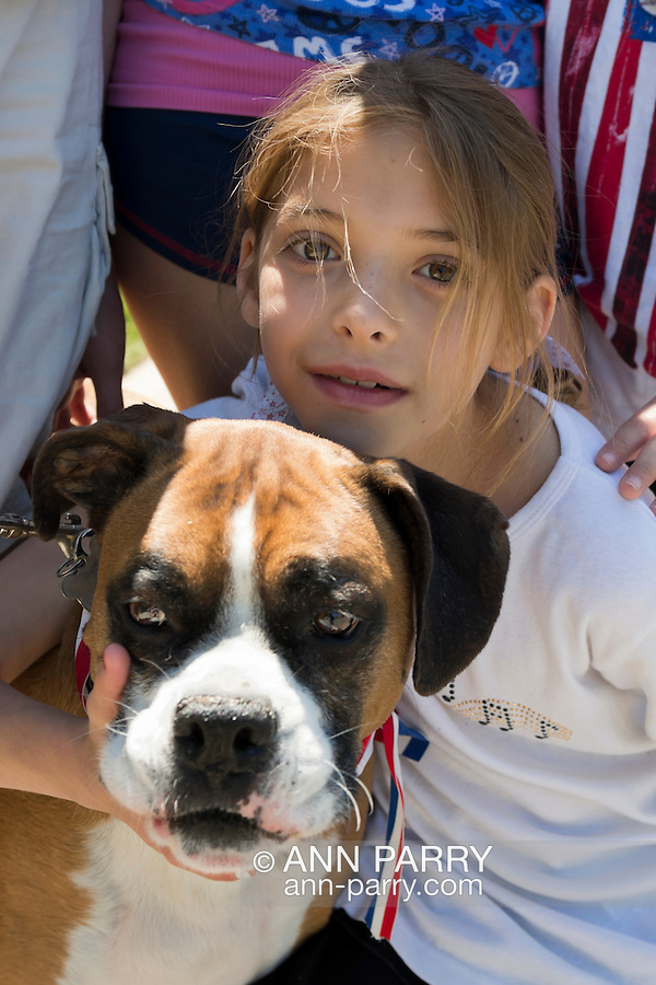Merrick, New York, USA. 27th May 2013. SARA MANSON, 8, of Merrick and boxer dog Harley Manson are watching the Annual Memorial Day Parade 2013, hosted by American Legion Merrick Post No. 1282, and the ceremony at Merrick Veteran Memorial Park.