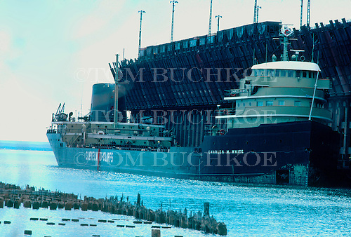 M/V Charles M White, part of the Cleveland-Cliffs Iron Company fleet, awaits a load of iron ore pellets at the LS&I ore dock in Marquette Michigan's upper harbor on Lake Superior. Circa 1970's