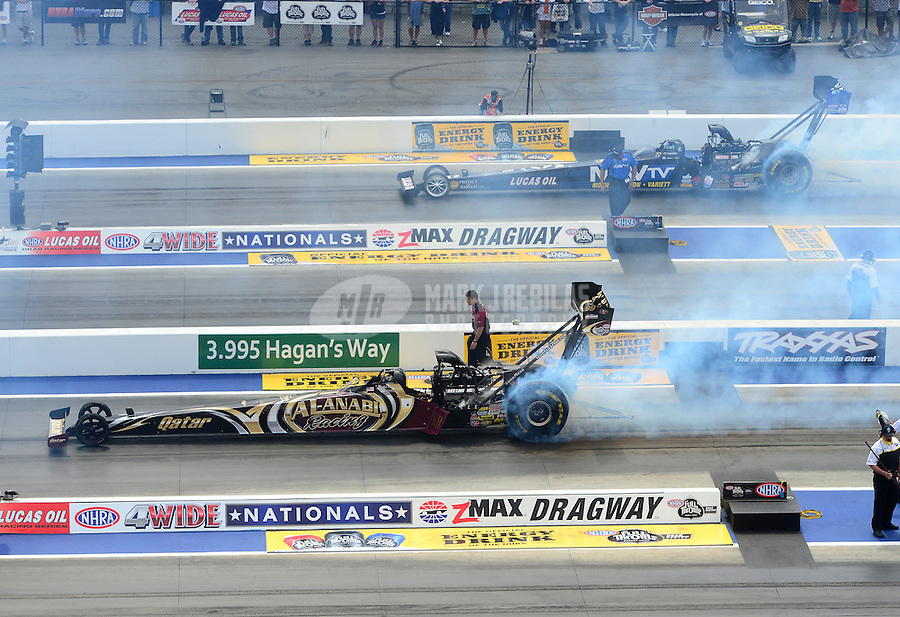 Apr. 15, 2012; Concord, NC, USA: NHRA top fuel dragster driver Khalid Albalooshi (near) does his burnout alongside Brandon Bernstein during eliminations for the Four Wide Nationals at zMax Dragway. Mandatory Credit: Mark J. Rebilas-