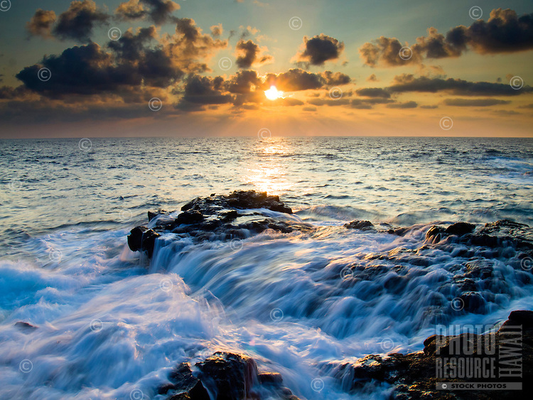 The setting sun's rays beam through clouds at Keahole Point, Big Island.