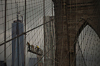 Workers fix some wires at the Brooklyn Bridge while it remains under maintenance one day before its 130th anniversary in New York,  May 23, 2013, Photo by Eduardo Munoz Alvarez / VIEWpress.