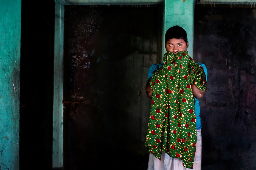 Masud Rana holds a dress of his mother Maksuda Begum (39) in front of the site at which Maksuda and Masud's sister Rojina (20), were killed the Tazreen Fashions factory fire in Ashulia, Bangladesh.