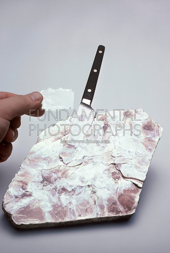 MUSCOVITE MICA CLEAVAGE<br /> KAl3Si3O10(OH)2- A Disilicate (Phyllosilicate).<br /> A large transparent cleavage flake is chipped away from a large muscovite rock with a flat blade knife.