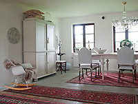 The dining room is traditionally furnished with the exception of an Eames rocking chair beside the white painted cupboard