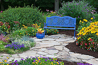 63821-21712 Blue bench, blue pot, and stone path in flower garden.  Black-eyed Susans (Rudbeckia hirta) Red Dragon Wing Begonias (Begonia x hybrida)  Zinnias, Homestead Purple Verbena (Verbena canadensis), New Gold Lantana (Lantana camara)  Butterfly Bushes, Sedum, zinnias, croton in container, Marion Co., IL