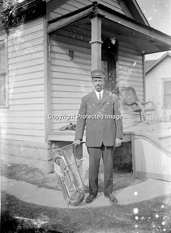 MUSICIAN BESIDE THE SHIPMAN HOUSE. The identity of the musician is uncertain, but his location is revealed by the address 851, which corresponds with the home of Edward and Clara Shipman at 851 University Avenue, located north of Vine Street between North Twelfth and Thirteenth Streets.<br />