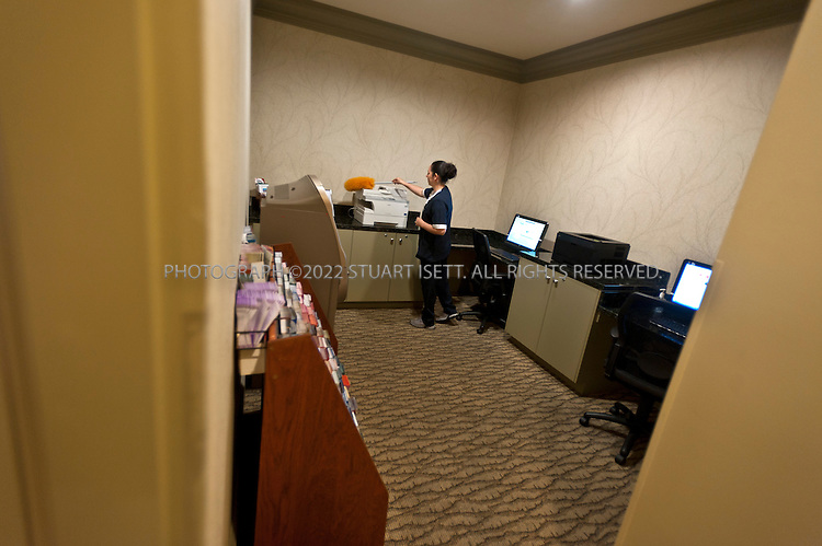 """9/27/2011--Seattle, WA, USA..Hotel employee Mayra Anguiano, 27, dusts the business center, just off the main lobby, at the Silver Cloud Hotel in Seattle, WASH. ..Business travelers armed with laptops, smartphones and wifi cards, are eschewing hotel business centers in favor of working in their rooms or the lobby, and hotels across the price spectrum have added the trappings of those business centers to where the guests are. Hotel business centers are still used by travelers who have a document or boarding pass to print, or need to check email and don't have their laptop, but they will usually get in and out quickly, rather than spend hours working there. And the business centers themselves are likely to be small rooms with just a few computers and printers. The Silver Cloud Hotel in Seattle, part of a ten-hotel chain in the Northwest, offers up two workstations and two printers, """"and business people barely use them,"""" said the hotel's general manager Chauncey DeVitis. The free WiFi and the copy machine behind the front desk seems to meet the needs of most business travelers these days, he said...©2011 Stuart Isett. All rights reserved."""
