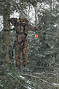 00105-043.05 Bowhunting (DIGITAL) Archer is in tree stand in balsam fir during snow storm.  Hunt, cold, late season, deer, winter.  V7R1