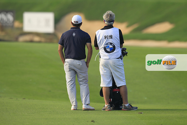 Alexander Levy (FRA) and caddy Bo wait to play his 2nd shot on the 16th hole during Sunday's Final Round of the 2014 BMW Masters held at Lake Malaren, Shanghai, China. 2nd November 2014.<br /> Picture: Eoin Clarke www.golffile.ie